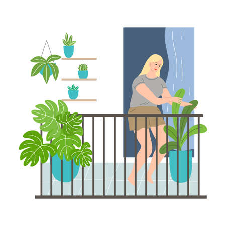 Smiling woman standing on balcony and taking care of plants in pots