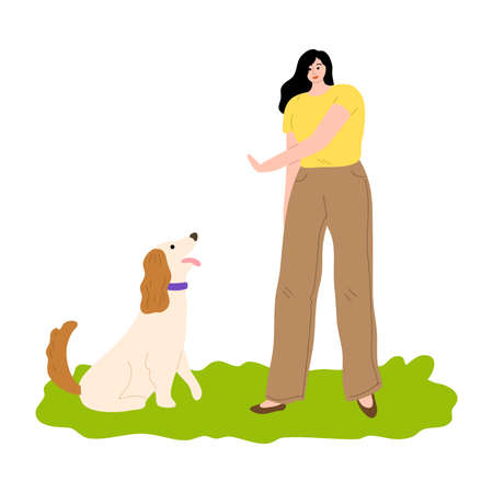 Woman training her dog and showing gesture to sit outdoor
