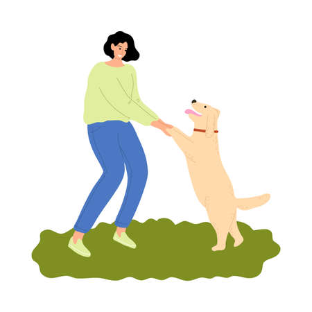 Woman training her dog and holding paws outdoor during walk