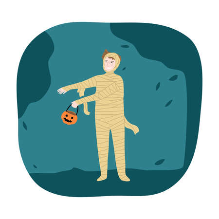 Boy in mummy costume for Halloween holiday standing and holding pumpkin in hand