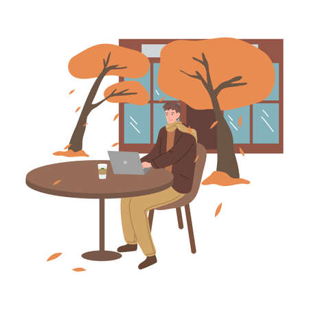 Smiling man sitting in street cafe and working on laptop in autumn city