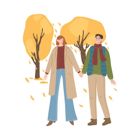 Young couple walking, holding hands and enjoying life in autumn park