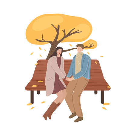 Young couple sitting on bench, holding hands and enjoying life in autumn park