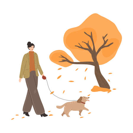 Happy young girl walking dog and enjoying life in autumn park