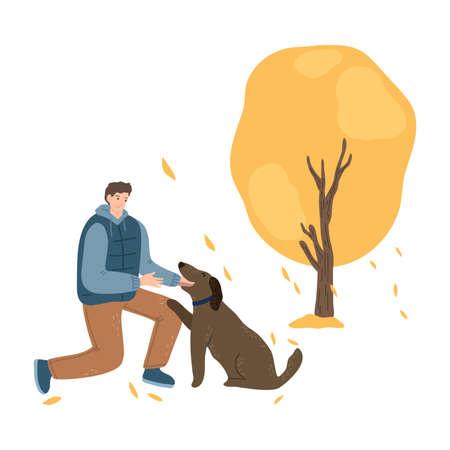 Man walking and training dog and enjoying life in autumn park