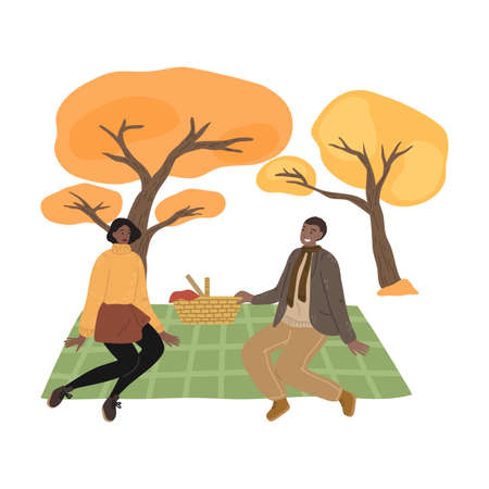 Young couple sitting on ground, having picnic and enjoying life in autumn park