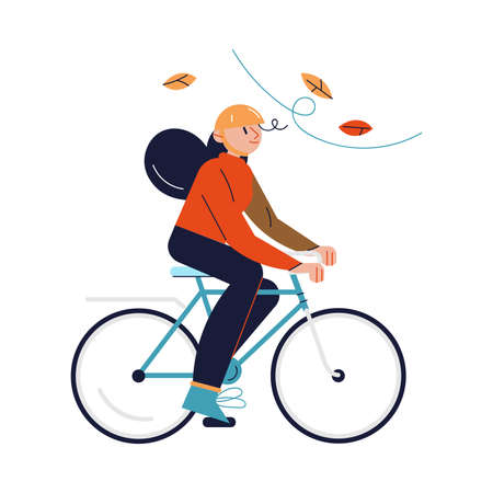 Smiling girl in helmet riding bicycle during leaf fall in autumn