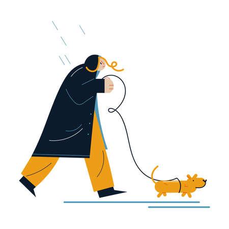 Woman in raincoat walking dog during rain in autumn