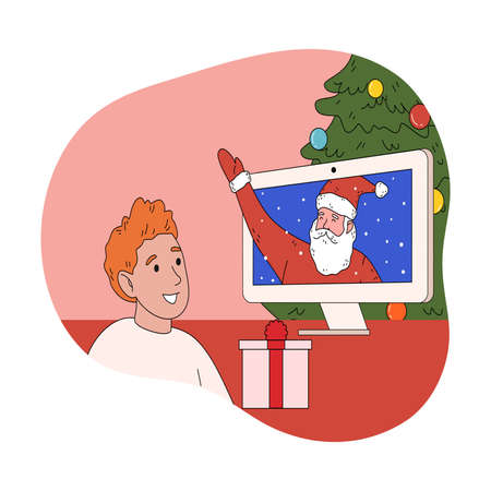 Happy boy sitting at home and chatting with Santa online on laptop during videocall