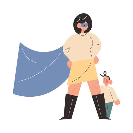 Confident young mother in superhero costume standing with small baby son standing behind