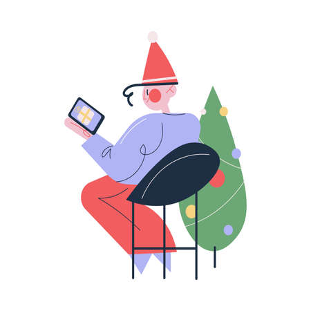 Happy young man in festive cap sitting and celebrating Christmas or new Year holiday online