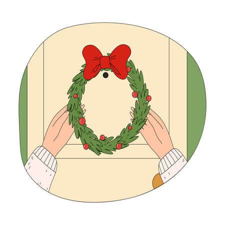 Human hands putting hanging ornate wreath on door during Christmas celebration
