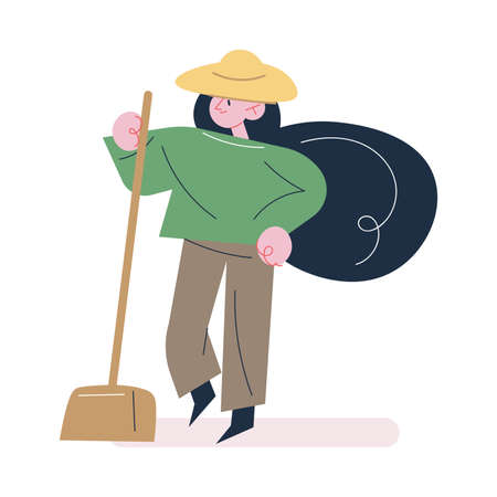 Woman gardener in working clothes and hat standing with shovel