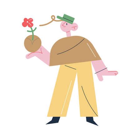 Man gardener standing and holding flower in soil in hand during gardening