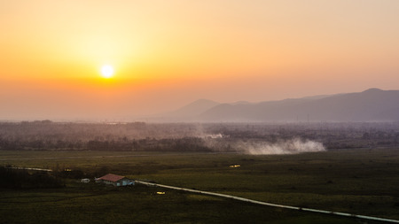Sunset landscape with orange sky, smoke and the silhouettes of the hills in the background