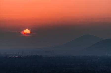 Beautiful sunset landscape with the silhouettes of the hills in the background and sun covered by clouds