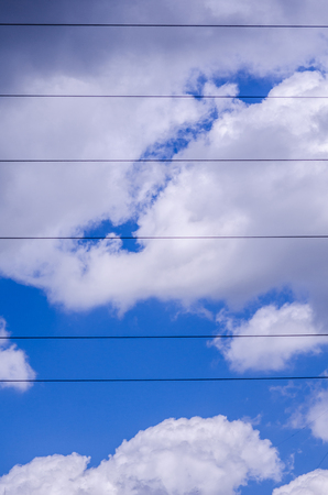 Power line cables running symmetrically across the sky against blue sky background with wonderful shaped white and grey clouds Banque d'images