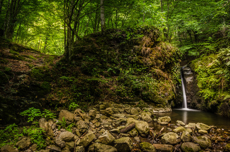 Waterfall in Carpathian Mountains flowing off a gully carved in a large rock