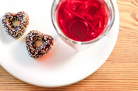 Two heart-shaped chocolate cookies with colorful candy sprinkles on top, glass of natural sour cherry red juice and a white plate on a wooden tabletop, top view Banque d'images