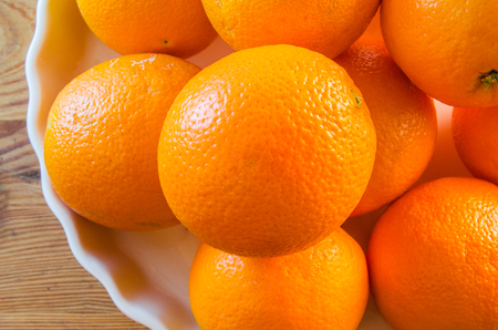Oranges stacked onto porcelain plateau on wooden tabletop, top view