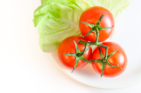 Three cherry tomatoes with stems, green letuce leaves and a white plate, isolated on white tabletop background surface, top view