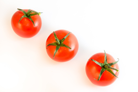 Three small cherry tomatoes with stems arranged diagonally isolated on white tabletop background surface, top view