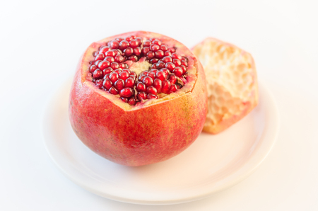 Ripe red pomegranate opened visible seeds on a white plate in foreground isolated on white background out-of-focus blurred Banque d'images
