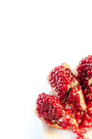 Ripe pomegranate, three slices, top view with copy space, visible seeds on a white plate in corner, isolated on white background