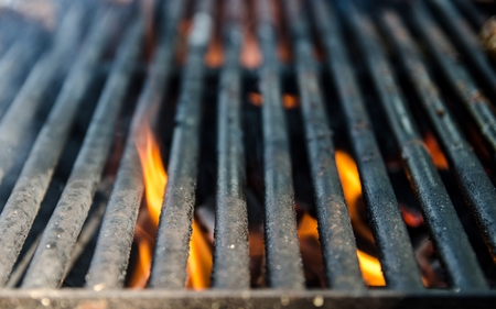 Grill bbq close up and bright hot flames, outside summer cookout, empty barbecue burning wood with smoke, blurred fire and charcoal briquettes Banque d'images