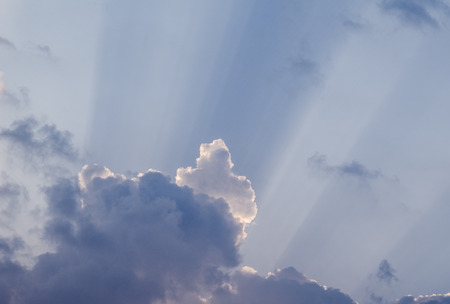 Amazing sun rays penetrating through beautiful clouds on the blue sky in a sunny day. Beautiful cloudscape background great for your graphic design project