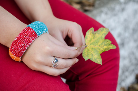 Girl in red pants wearing a big bracelet on her wrist and beautiful heart ring on her finger is holding a colorful autumn leaf in her hands Banque d'images