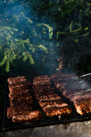 Grilled minced meat rolls called Mici or Mititei in traditional Romanian cuisine cooked outside on a hot summer day on barbeque grill with green small pine trees in background Banque d'images