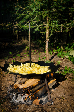 Potatoes fried in oil over a wood fire, cooked outside on unusual round curved metal steel disk with legs and handle. Romanian spring summer and autumn grill and barbecue tradition of cooking for friends and family outdoors in the nature