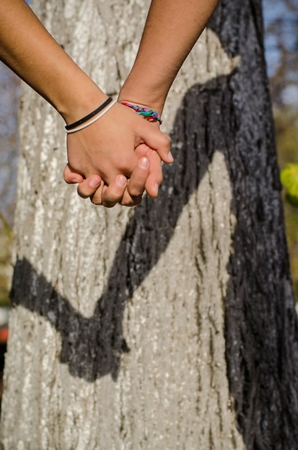 Couple in love holding hands in a hot summer day outside in the nature. Young girl and boy with hands together expressing beautiful feelings. Shadow of couple hands falls on a blurry tree trunk