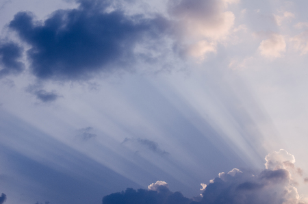 Unusual sun rays penetrating through beautiful thick fluffy clouds on the blue sky in a hot summer day. Beautiful cloudscape background or backdrop for your graphic design