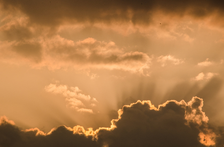 Beautiful sunset sun rays penetrating through fluffy clouds on orange sky in a hot summer day at dusk. Awesome cloudscape background or backdrop wallpaper for your graphic design project Banque d'images