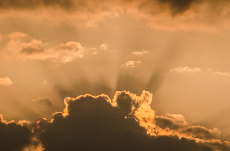 Wonderful sunset sun rays penetrating through dark clouds on orange sky in a hot summer day at dusk. Beautiful cloudscape background or backdrop for your graphic design project Banque d'images