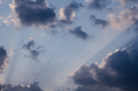 Wonderful sun rays penetrating through fluffy clouds on the blue sky in a hot summer day. Beautiful cloudscape background great for your graphic design project