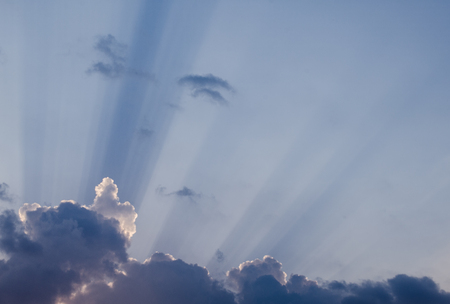 Beautiful sun rays penetrating through beautiful thick fluffy clouds on the blue sky in a hot summer day. Awesome cloudscape background great for your graphic design project