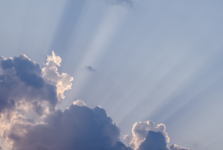 Wonderful sun rays penetrating through beautiful thick fluffy clouds on the blue sky in a hot summer day. Awesome cloudscape background great for your graphic design project