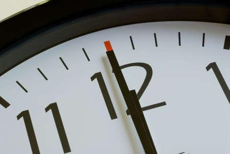 白い顔に黒い壁時計 o クロック正午 12 時を示しています