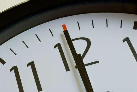 12 o'clock: a black wall clock with a white face shows 12 o clock noon