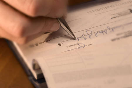 a closeup of a womans hand and pen writing out a check