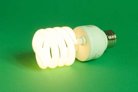 a compact fluorescent lightbulb on a green background