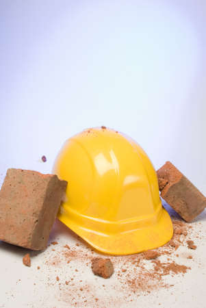 depiction: depiction of a hardhat breaking the fall of a brick