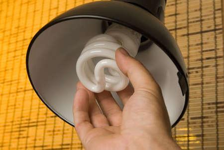 A hand installs a compact fluorescent light bulb into a desk lamp 스톡 콘텐츠