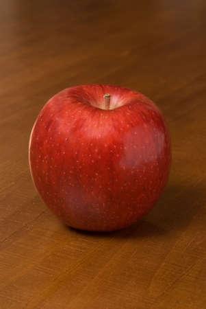 una sola manzana roja sobre una mesa de madera Foto de archivo - 2642047