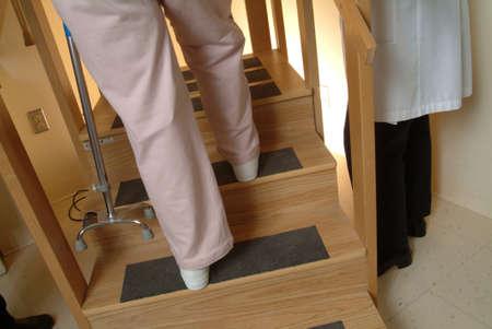 リハビリ患者の足のクローズ アップ援助者と 4 点杖の助けを借りて二階に歩くことを学習する彼女は、