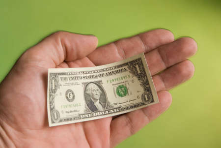 transact: a hand holding a miniature United States one dollar bill depicting the shrinking United States dollar Stock Photo