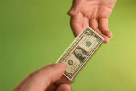 shrinking: one person hands to another a miniature United States one dollar bill depicting the shrinking United States dollar Stock Photo